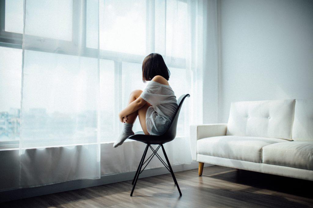 Acceptation. Femme de dos assise sur une chaise, les mains autour des genoux